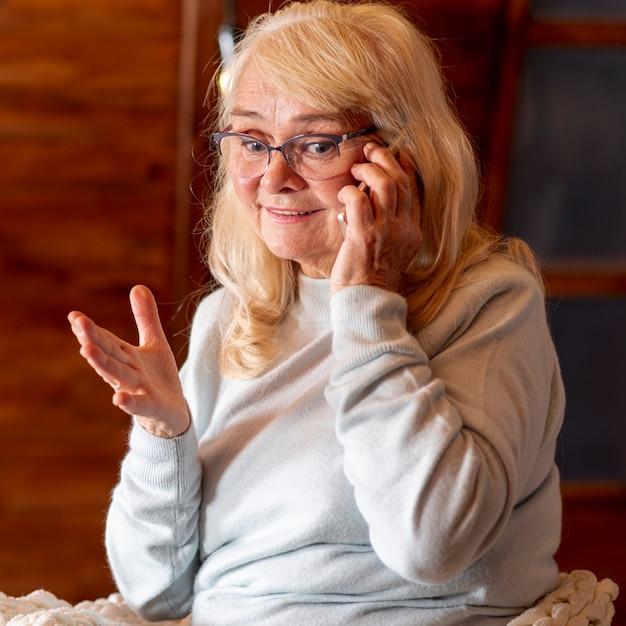 Vue de face d'une femme âgée parlant au téléphone Photo gratuit