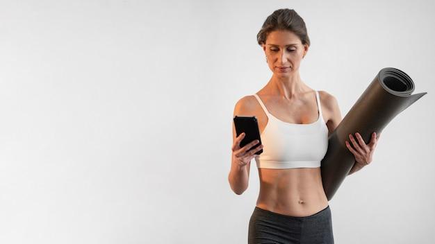Vue De Face De La Femme à L'aide De Smartphone Tout En Tenant Un Tapis De Yoga Avec Espace De Copie Photo gratuit