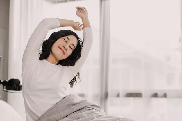 Vue de face d'une femme asiatique au matin. elle s'étire la main et le corps sur le lit Photo Premium