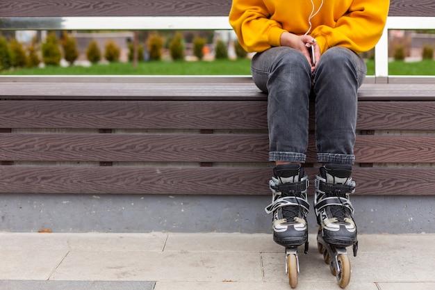 Vue de face d'une femme sur un banc portant des patins à roues alignées Photo gratuit