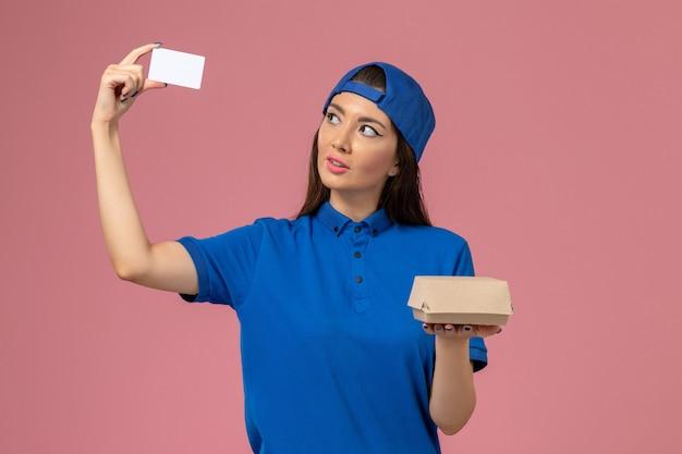 Vue De Face Femme Courrier En Cape Uniforme Bleu Tenant Peu De Colis De Livraison Avec Carte En Plastique Sur Mur Rose Clair, Travail De Prestation De Services Des Employés Photo gratuit