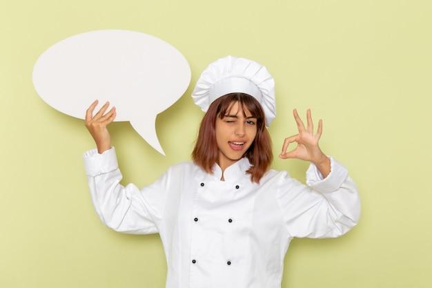 Vue De Face Femme Cuisinier En Costume De Cuisinier Blanc Tenant Un Grand Panneau Blanc Sur Un Bureau Vert Photo gratuit