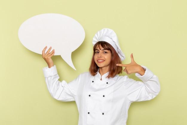 Vue De Face Femme Cuisinier En Costume De Cuisinier Blanc Tenant Un Grand Panneau Blanc Sur La Surface Verte Photo gratuit