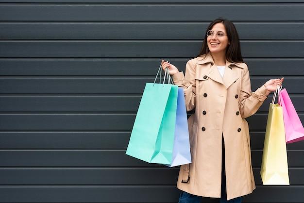 Vue De Face De La Femme Avec Des Lunettes Tenant Beaucoup De Sacs à Provisions Avec Espace Copie Photo gratuit
