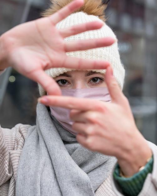 Vue De Face De La Femme Avec Un Masque Médical Faisant Le Cadre Avec Les Mains Photo gratuit