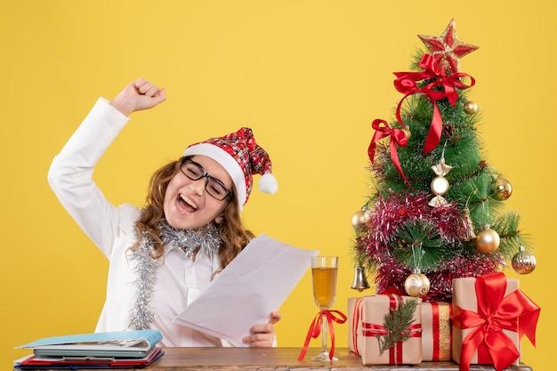 Vue De Face Femme Médecin Assis Avec Arbre De Noël Présente Et Tenant Des Documents Sur Fond Jaune Avec Arbre De Noël Et Coffrets Cadeaux Photo gratuit