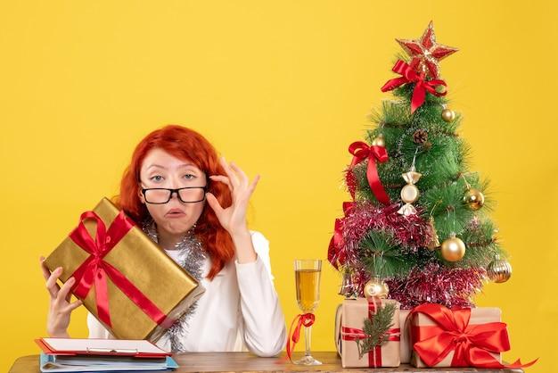 Vue De Face Femme Médecin Assis Avec Des Cadeaux De Noël Et Arbre Sur Un Bureau Jaune Photo gratuit