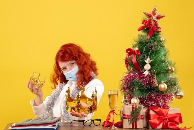 Vue De Face Femme Médecin Assis Avec Des Cadeaux De Noël Et Tenant Des Couronnes Sur Fond Jaune Photo gratuit