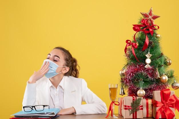 Vue De Face Femme Médecin Assis Dans Un Masque De Protection Bâillant Sur Fond Jaune Avec Arbre De Noël Et Coffrets Cadeaux Photo gratuit