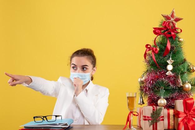 Vue De Face Femme Médecin Assis Dans Un Masque De Protection Sur Un Bureau Jaune Avec Arbre De Noël Et Coffrets Cadeaux Photo gratuit