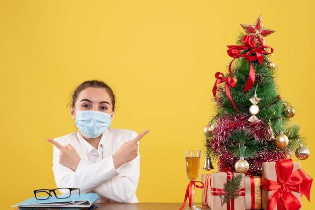 Vue De Face Femme Médecin Assis Dans Un Masque De Protection Souriant Sur Fond Jaune Avec Arbre De Noël Et Coffrets Cadeaux Photo gratuit