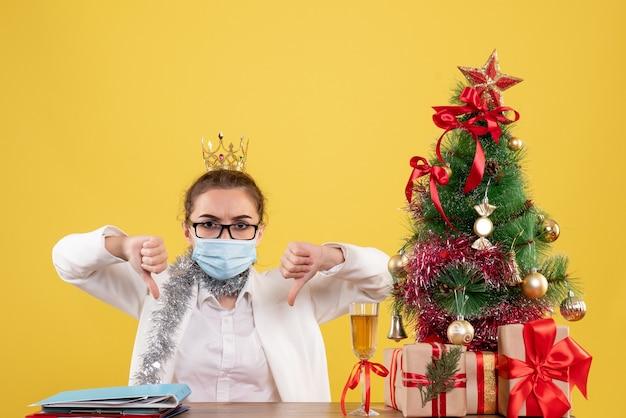 Vue De Face Femme Médecin Assis Dans Un Masque Stérile Sur Un Bureau Jaune Avec Arbre De Noël Et Coffrets Cadeaux Photo gratuit