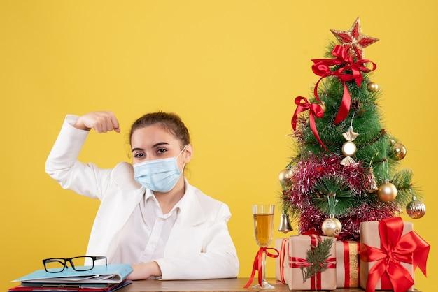 Vue De Face Femme Médecin Assis Dans Un Masque Stérile Fléchissant Sur Fond Jaune Avec Arbre De Noël Et Coffrets Cadeaux Photo gratuit