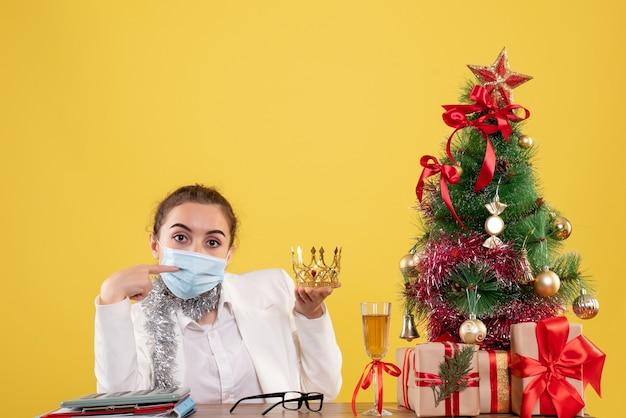 Vue De Face Femme Médecin Assis Dans Un Masque Stérile Tenant La Couronne Sur Fond Jaune Avec Arbre De Noël Et Coffrets Cadeaux Photo gratuit