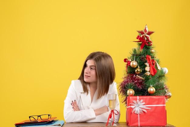 Vue De Face Femme Médecin Assis Devant Sa Table Sur Un Bureau Jaune Avec Arbre De Noël Et Coffrets Cadeaux Photo gratuit