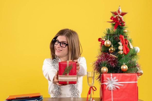 Vue De Face Femme Médecin Assis Devant La Table Avec Des Cadeaux Et Arbre Sur Fond Jaune Avec Arbre De Noël Et Coffrets Cadeaux Photo gratuit
