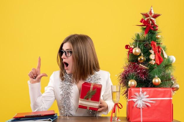 Vue De Face Femme Médecin Assis En Face De La Table Avec Des Cadeaux Et Arbre Sur Un Bureau Jaune Avec Arbre De Noël Et Coffrets Cadeaux Photo gratuit