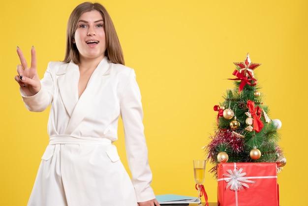 Vue De Face Femme Médecin Debout Autour De La Table Avec Petit Arbre De Noël Sur Fond Jaune Avec Arbre De Noël Et Coffrets Cadeaux Photo gratuit