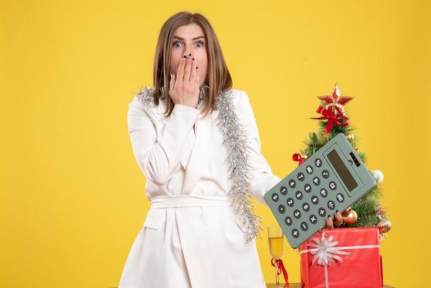 Vue De Face Femme Médecin Debout Et Tenant La Calculatrice Sur Fond Jaune Avec Arbre De Noël Et Coffrets Cadeaux Photo gratuit