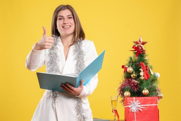 Vue De Face Femme Médecin Debout Et Tenant Des Documents Sur Un Bureau Jaune Avec Arbre De Noël Et Coffrets Cadeaux Photo gratuit