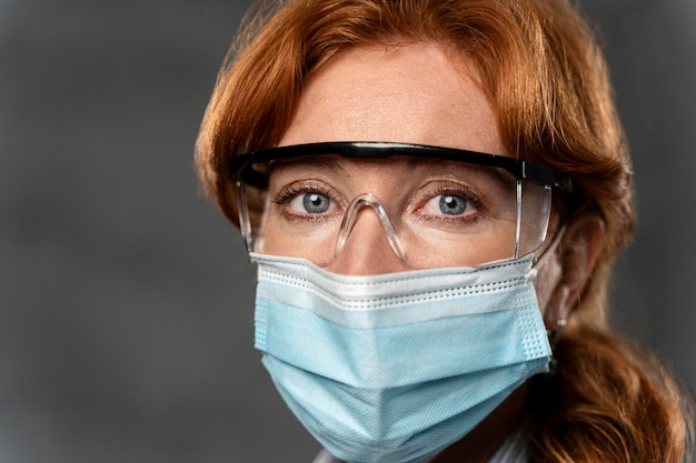Vue De Face De La Femme Médecin Avec Masque Médical Et Lunettes De Sécurité Photo gratuit