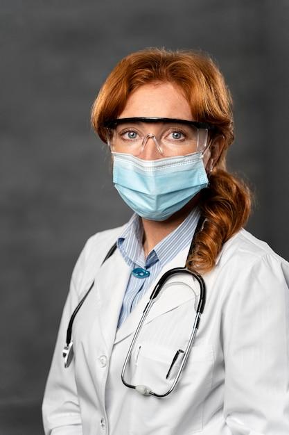 Vue De Face De La Femme Médecin Avec Masque Médical, Stéthoscope Et Lunettes De Sécurité Photo gratuit