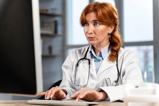 Vue De Face De La Femme Médecin à La Recherche De Trucs Sur Ordinateur Au Bureau Photo gratuit