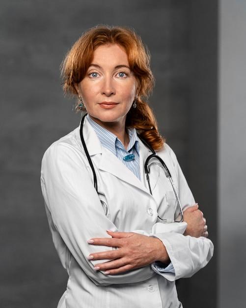 Vue De Face De La Femme Médecin Avec Stéthoscope Posant Les Bras Croisés Photo gratuit