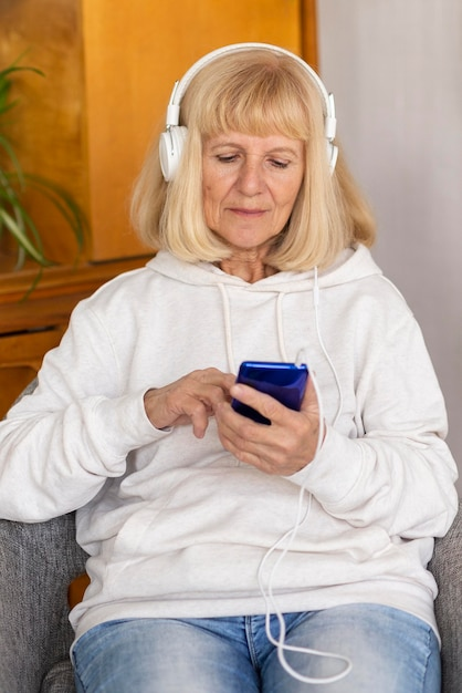 Vue De Face D'une Femme Plus âgée Avec Un Casque Et Un Smartphone Photo gratuit
