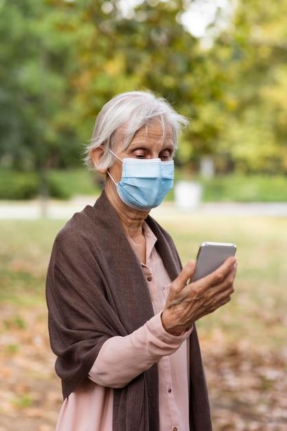 Vue De Face D'une Femme Plus âgée Avec Masque Médical Tenant Le Smartphone Photo gratuit