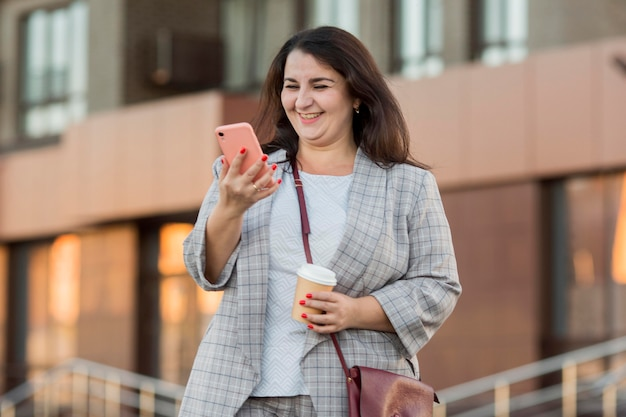 Vue De Face Femme Regardant Son Téléphone Photo gratuit