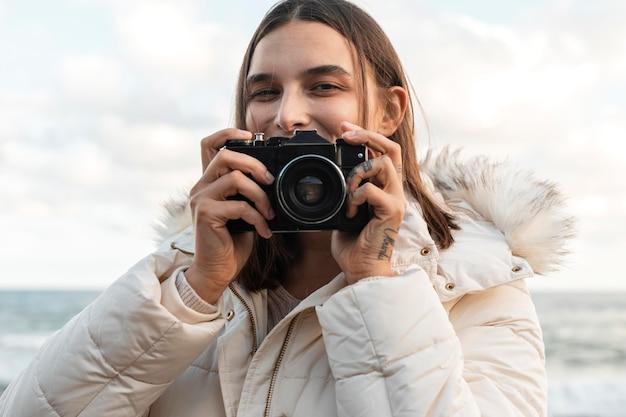 Vue De Face De La Femme Souriante Avec Caméra à La Plage Photo gratuit