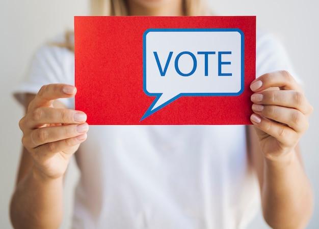 Vue de face d'une femme tenant un message de vote Photo gratuit