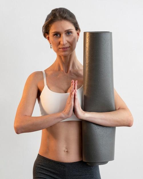 Vue De Face De La Femme Tenant Un Tapis De Yoga Tout En Faisant Une Pose Photo gratuit
