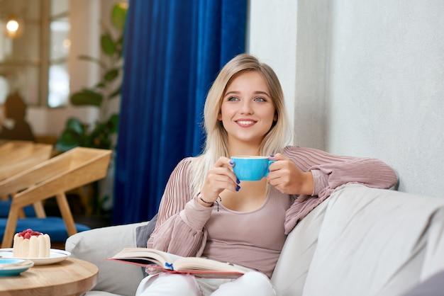 Vue De Face D'une Fille Blonde Souriante, Buvant Un Café Savoureux Assis Sur Un Canapé Blanc. Photo Premium