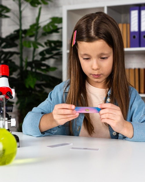 Vue De Face De Fille Avec Microscope Et Tubes à Essai Photo Premium