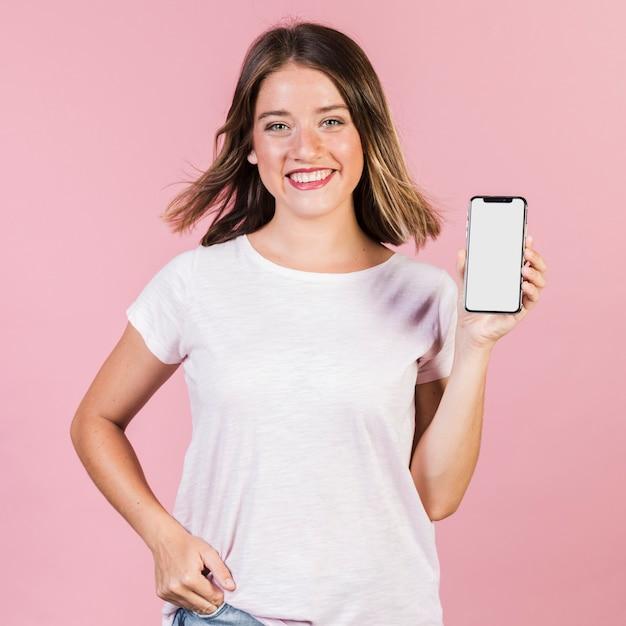 Vue de face fille montrant son téléphone Photo gratuit