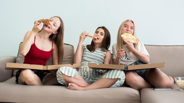 Vue de face des filles assises sur un canapé et mangeant une pizza Photo gratuit