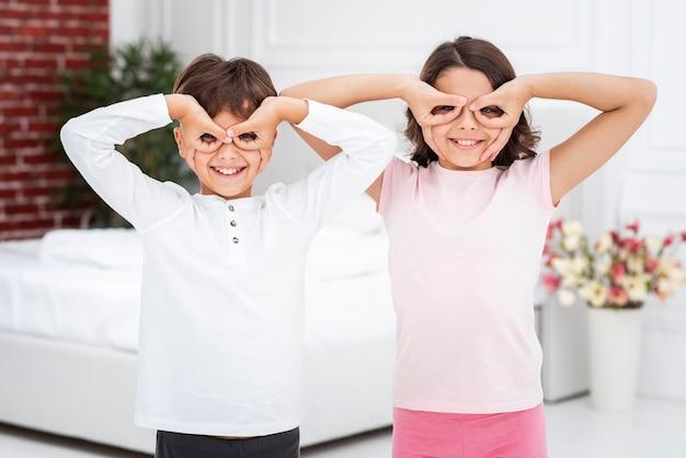 Vue de face des frères et sœurs enjoués s'amusant à la maison Photo gratuit