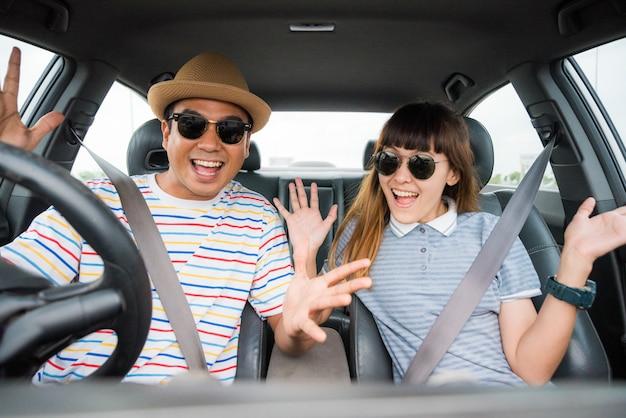 Vue De Face De Funny Moment Couple Asiatique Homme Et Femme Assise Dans La Voiture. Profitant Du Concept De Voyage. Photo Premium