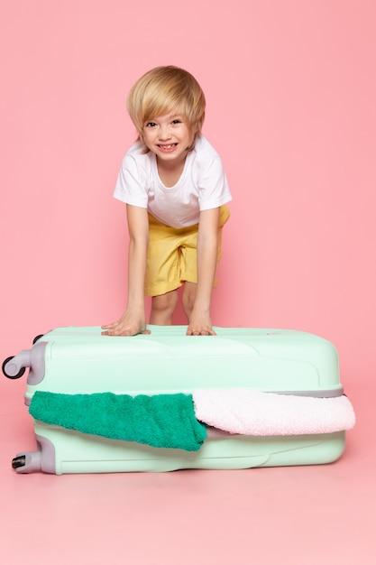 Vue De Face Garçon Blond Adorable Mignon Debout Sur Le Sac Bleu Sur Rose Photo gratuit