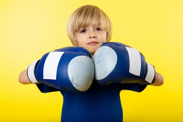 Une Vue De Face Garçon Blond En Gants Bleus Et T-shirt Bleu Sur Le Mur Jaune Photo gratuit