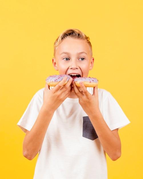 Vue de face garçon essayant de manger deux beignets à la fois Photo gratuit