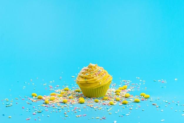 Une Vue De Face Gâteau Jaune Avec De Petites Particules De Bonbons Colorés Sur Un Bureau Bleu, Gâteau Biscuit Sucré Photo gratuit