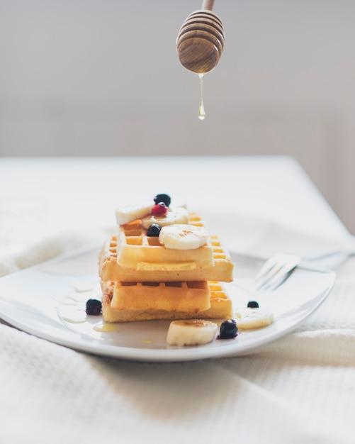 Vue de face des gaufres et une cuillère à miel Photo gratuit