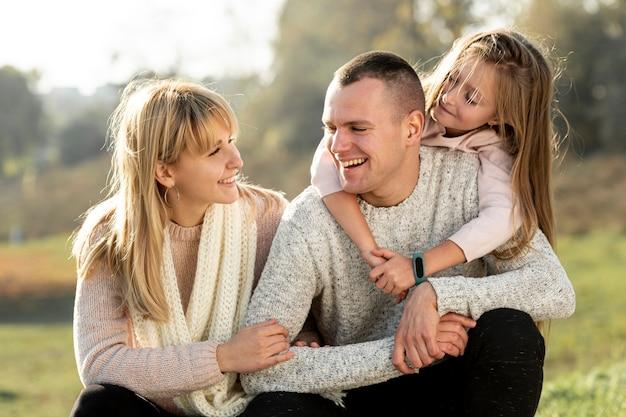 Vue de face heureuse jeune famille se regardant Photo gratuit