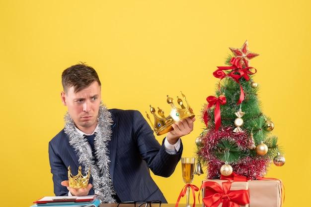 Vue De Face De L'homme D'affaires Comparant Ses Couronnes Assis à La Table Près De L'arbre De Noël Et Présente Sur Mur Jaune Photo gratuit
