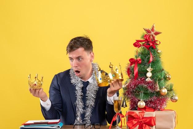 Vue De Face De L'homme D'affaires étonné à La Recherche De Couronnes Assis à La Table Près De L'arbre De Noël Et Présente Sur Mur Jaune Photo gratuit