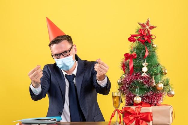 Vue De Face De L'homme D'affaires Faisant De L'argent Signe Avec Les Doigts Assis à La Table Près De L'arbre De Noël Et Présente Sur Jaune Photo gratuit
