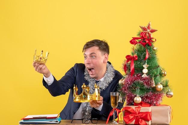 Vue De Face De L'homme D'affaires à La Recherche De Couronnes Assis à La Table Près De L'arbre De Noël Et Présente Sur Jaune Photo gratuit